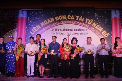 Phó Chủ tịch UBND tỉnh Long An - Phạm Văn Cảnh (thứ 5, trái qua) và nguyên Phó Bí thư Thường trực Tỉnh ủy - Đỗ Hữu Lâm (thứ 2, phải qua) tặng hoa cho các Ban Đờn ca tài tử tham gia liên hoan