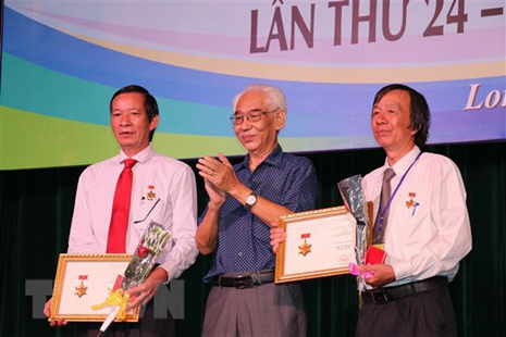 Họa sỹ Trần Khánh Chương (giữa) trong một buổi khai mạc triển lãm mỹ thuật. (Nguồn: TTXVN)